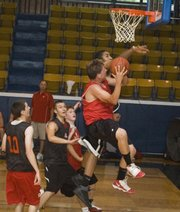 Austin Vickers tries to avoid a Lansing defender on a drive to the rim at the Rockhurst summer league.