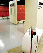 A large fan helps to dry the newly painted floor of the Bonner Springs High School football locker room. The scuffed concrete near the base of the fan gives a glimpse of what the entire floor used to look like.