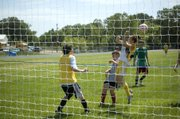 Alex Bartels, playing defense on Thursday at Tonganoxie High soccer camp, tries to head the ball away from in front of the goal.