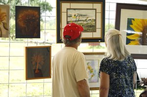 Visitors to the Sunflower ArtFest admire the special exhibit of sunflower-themed work.