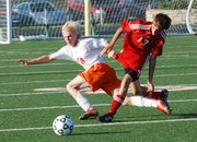 Tonganoxie's Evan Stilgenbauer (13) and Bonner Springs' Cody Duncan (10) collide while battling for possession of the ball during the first half of the Braves' 4-0 victory Tuesday at BSHS.