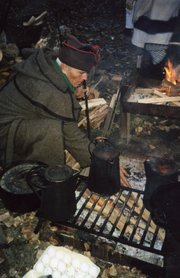 Jim Stanley, of Bonner Springs, cooks over an open fire while re-enacting a portion of the Lewis and Clark expedition. Stanley has been involved in historic re-enactments for more than 30 years and a few years ago participated in a four-year re-enactment.