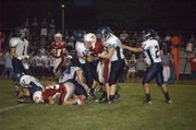 Mill Valley High's Jeremy Spalding (45) and Zach Callahan (56) sandwich Tonganoxie quarterback Brady Waldeier Friday night in the Jaguars' 57-12 defeat of the Chieftains.