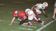THS defensive back Adrian Whittington takes down Lansing's Parker Gibson in the Chieftains' 42-24 road loss on Friday.