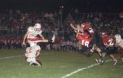Tonganoxie High kicker Amos White knocks a 27-yard field goal past the outstretched arms of the Lions in the second quarter of the Chieftains' 42-24 loss at Lansing on Friday.