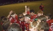 Members of the Tonganoxie High boys soccer team celebrate after earning their second win of the season with a 2-1 regional playoff victory on Oct. 25 at Perry-Lecompton.