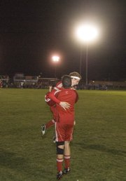 Zack Tallent jumps onto teammate Dallon Price moments after Tonganoxie defeated Perry-Lecompton, 2-1, for its second victory of the season.