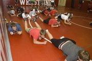 Tonganoxie High wrestlers do army crawls as part of their warm-ups Monday at practice.