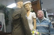 "Mary Ellen Ballard stands next to the mannequins wearing her mother and father's wedding-day clothes at the Basehor Historical Museum. The scene, part of the museum's ""Wedding Wonderland"" exhibit, depicts their June 1944 wedding in a living room."
