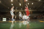 Basehor-Linwood High senior guard Evan Theno draws a charge against Tonganoxie senior guard Jeremy Carlisle in the first half of the Bobcats' 62-30 victory to open the season Friday night at Basehor.