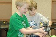 Patrick Dalton and Douglas Hotter examine their robot during the Shawnee Park and Recreation robotics class Monday.