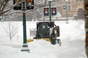 Baker University crews work to clear snow from the sidewalks around campus Monday morning. A couple of inches of snow had fallen this morning with more expected to fall later today.