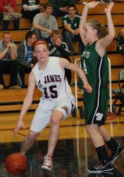 St. James Academy freshman Arianna Person drives past De Soto's Jesse Spencer during De Soto's 44-29 victory.