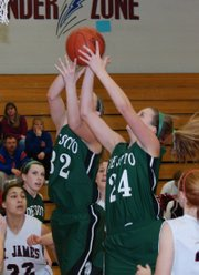 De Soto's Katie Gorman (32) and Ashley Gorman (24) battle for a rebound in De Soto's 44-29 victory Monday at St. James Academy.