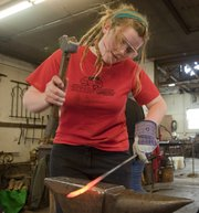 Danielle Volle, 20, an artist with Van Go Mobile Arts, forges a piece of iron planned for the Black Jack Gate Thursday, Feb. 17, 2011, at Walt Hull Ironworks.