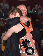 Bonner Springs senior Caleb Seaton hugs his father, BSHS assistant coach Jerry Seaton, after winning the 125-pound state championship.