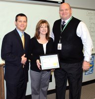 De Soto High School Communications Arts teacher Donna Rhodes accepts her certificate for Teacher of the Year from Superintendent-elect Doug Sumner (left) and Principal Dave Morford. Photo courtesy of USD 232.