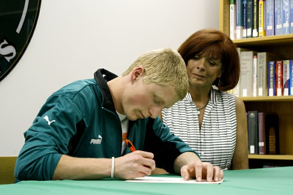 Greg Henning, a senior at De Soto High School, signs a letter of intent to play soccer for Baker University as his mother, Chris Henning, watches on Wednesday, March 30. Henning, whose older brother currently plays for Baker, is excited about joining the close-knit team.