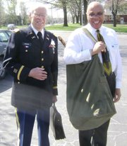 World War II veteran Nelson Borden, left, and Trailridge Middle School Principal Larry King carry artifacts into the school last Tuesday before eighth-grade social studies students interviewed Borden and eleven other veterans.