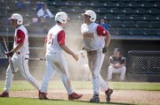 Shane Levy congratulates Dylan Puhr after Puhr slid home to score Tonganoxie's ninth run of the game against Holton in the top of the sixth inning Thursday afternoon at CommunityAmerica Ballpark in Kansas City, Kan. Holton came back to win the game, 10-9.