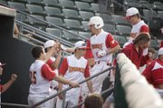 Tonganoxie High senior Corey Klinkenberg is congratulated by his teammates as he returns to the dugout after scoring a run against Perry-Lecompton on Friday at CommunityAmerica Ballpark. The Chieftains defeated PLHS, 8-1, in a Butch Foster Memorial Baseball Classic consolation semifinal.