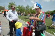 "A balloon artist who goes by the name of ""Balloonman"" makes a balloon spider for Jacob Noyes, 4, while Noyes' grandfather, Greg Harr, watches."