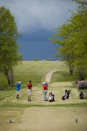 A group of golfers, including Tonganoxie High's Colby Yates, wait to tee off Thursday at Lake Perry Country Club as dark clouds roll in. A thunderstorm shortened the Perry-Lecompton Invitational to nine holes and THS finished third.
