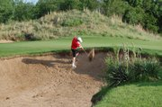 Tonganoxie High sophomore Aaron Williams strikes a shot out of a bunker at the Class 4A state tournament on Monday at Hutchinson. The Chieftains finished second in the team standings at Prairie Dunes Country Club with a four-player score of 332.