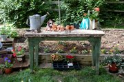 A potting bench made with architectural salvage wood decorates a vegetable garden in the corner of Richard and Elaine Jones' backyard garden. The couple cook with herbs and vegetables from the garden, and they said their grandchildren enjoy picking strawberries.