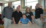 Caleb Seaton, seated, will wrestle in college at Fort Hays State University. Joining the Bonner Springs High School senior at his signing ceremony are, standing, from left:BSHSActivities Director John Hilton, father and BSHSassistant coach Jerry Seaton, mother Cheryle Seaton, and BSHScoach Brandon Jobe.