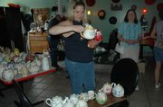 Jaime Potts of Piper checks out some teapots at Madame Hatter's Tea Room on Tuesday. She said the teapots would help her with teas she organizes for her church.