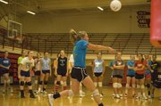 A rising THS sophomore, Caly Ingle-Maxwell bumps the ball upward as her teammates watch during a drill on June 22 at Tonganoxie volleyball camp.