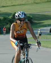 Sunita Gupta, Olathe, powers her way up a hill during the cycling portion of the Shawnee Mission Triathlon Sunday at Shawnee Mission Park. Gupta competed in the womens long course race.
