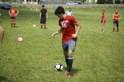 """Tyler Bartholomew runs through a ball handling drill on Thursday at THS """"Sokker Kamp."""""""