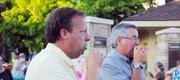 Sen. Tom Holland, left, and Baldwin City Mayor Ken Wagner play their kazoos during the kazoo-along Friday evening during the Baldwin Community Arts Council's Art Walk. About 100 people played kazoos to the tune of patriotic music during the event.