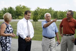 Kansas Secretary of Commerce Pat George (center left) listens as Darrel Zimmerman describes the layout of his Kill Creek Farm on Tuesday, July 26. State Senator Julia Lynn (R, Olathe) and De Soto Mayor Dave Anderson listened as well. Sec. George visited De Soto to speak to the Economic Development Council and then went on a tour of the town, stopping by Riverfest Park and the Sunflower Water Treatment facility among other sites.
