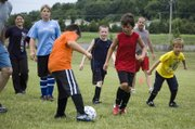 "Jerrod Lowe, 8, tries to control the ball as a crowd of campers and parents approach during the kids vs. parents game at THS youth ""Sokker Kamp."""