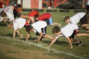 As a part of warmups Thursday night at Tonganoxie High youth football camp, campers line up for bear crawls before breaking off into station work.
