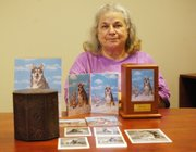Edie Ommerman sits with urns containing her dogs, Koda and Kong. Ommerman said she still talks to them, at times saying hello when she calls her answering machine to leave herself a reminder while away.