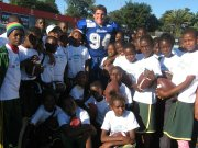 Matt Acree, a 2010 Mill Valley High School graduate and current Drake University football player, is surrounded by Tanzanian youths after playing in the first American football game on the African continent in May.