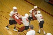 Tonganoxie High football linemen go through drills inside the THS east campus gymnasium on Monday afternoon as assistant coach Brad Shelton looks on. The Chieftains had to practice indoors on Monday after heavy morning rain.