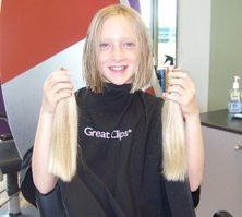 Brooke Koehler shows off her new hairstyle with her Locks of Love donations in each hand.