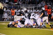 A pile of Baldwin High and De Soto players forms after a short yardage attempt by De Soto during the first half Friday night. De Soto won the game 28-7.