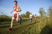 The Chieftains' Jeff Neal glances at the runners ahead of him as he rounds a turn Tuesday at the Tonganoxie Invitational. With a 18th-place finish, Neal was one of six THS boys to medal as Tonganoxie won the team title.