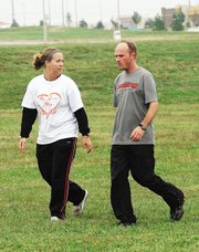 Melanie Enneking, left, Lansing High School cross country coach, was one of 480 people wearing T-shirts showing support for Bonner Springs High School senior Scintila Capalla at the Bonner Springs Invitational. Capalla is missing her senior season of cross country while battling osteosarcoma, a form of bone cancer.