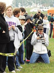 Scintila Capalla, in camouflage hat, was one of the faces in the crowd near the finish line at the Bonner Springs Invitational. Capalla, a Bonner Springs senior, fired the starting gun at the beginning of the varsity girls' race at the meet Saturday.