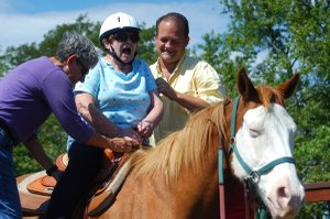 Danila Rock reacts to being atop a horse for the first time in more than 50 years as New Horizon Ranch riding instructor Ronda Wooden and CEO Brian Miller help situate her in the saddle. On Sept. 20 a wish-granting group enabled Rock, an 85-year-old resident at Sweet Life Shawnee, to ride a horse for the first time since she emigrated from Italy, where she rode daily in her youth.