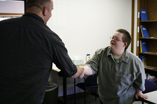 ACCESS House student Matt Runde shakes hands with De Soto USD 232 technology worker Aaron Pflughoft at the ACCESS House open house on Wednesday, Sept. 28. Runde, a new student at ACCESS House, was in charge of showing visitors the conference room and explaining what it is used for.
