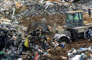 File photo. An average of 5,000 tons of trash is buried each day at the Johnson County Landfill, according to Deffenbaugh Industries Inc., which owns and operates the 1,000-acre site. As incoming trucks dump new loads of trash, heavy equipment levels and compacts the waste.