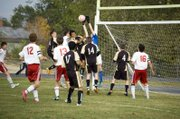 Tonganoxie High junior goalkeeper Keaton Truesdell leaps up to knock the ball away in a crowd following a first-half corner kick in the Chieftains&#39; 4-2 Monday home win.